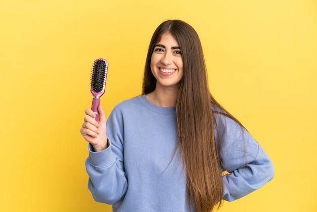 Młoda kaukaska kobieta trzyma szczotkę do włosów na białym tle na niebieskim tle, pozuje z rękami na biodrach i uśmiecha się