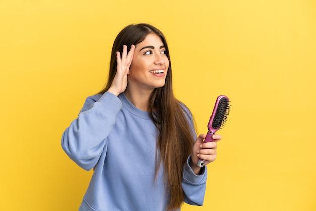 Młoda kaukaska kobieta trzyma szczotkę do włosów na białym tle na niebieskim tle, słuchając czegoś, kładąc rękę na uchu