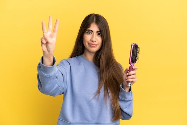 Młoda kaukaska kobieta trzyma szczotkę do włosów na białym tle na niebieskim tle szczęśliwa i liczy trzy palcami
