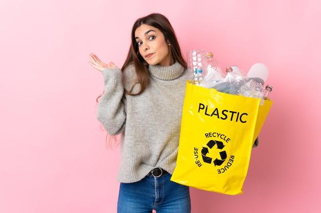 Młoda kaukaska kobieta trzyma torbę pełną plastikowych butelek do recyklingu na różowo, mając wątpliwości podczas podnoszenia rąk