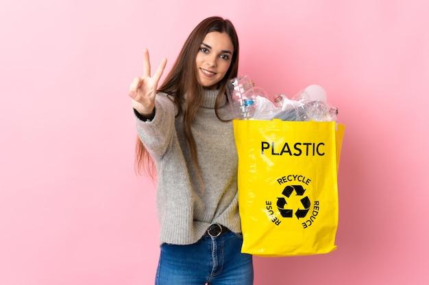 Młoda kaukaska kobieta trzyma torbę pełną plastikowych butelek do recyklingu na różowo, uśmiechając się i pokazując znak zwycięstwa