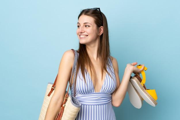 Młoda kaukaska kobieta trzyma torbę plażową i letnie sandały odizolowane na niebieskim tle patrząc z boku