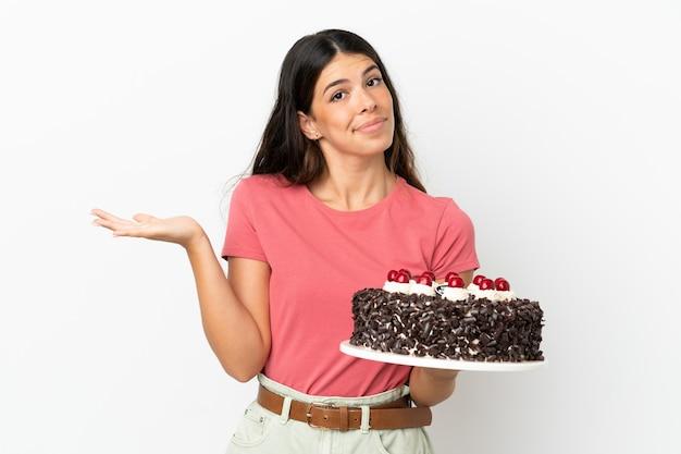 Młoda kaukaska kobieta trzyma tort urodzinowy na białym tle, mając wątpliwości podczas podnoszenia rąk