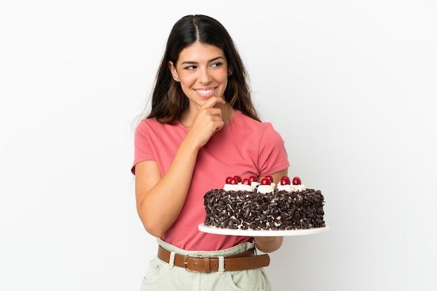 Młoda kaukaska kobieta trzyma tort urodzinowy na białym tle, patrząc w bok i uśmiechając się