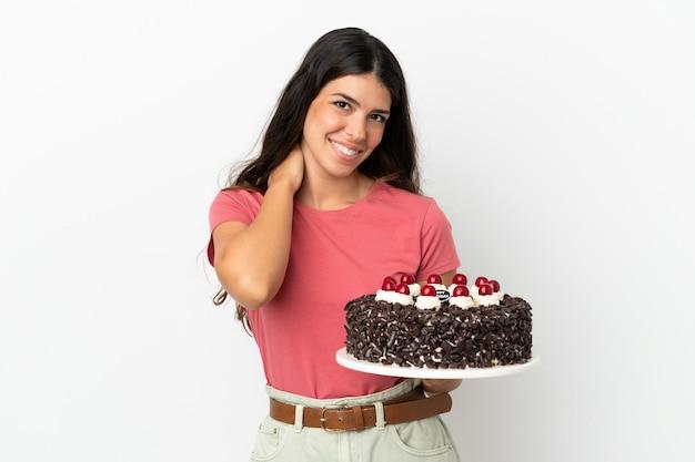 Młoda kaukaska kobieta trzyma tort urodzinowy na białym tle śmiejąc się