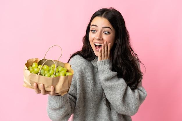 Młoda kaukaska kobieta trzyma winogrona na białym tle na niebieskim tle z zaskoczeniem i zszokowanym wyrazem twarzy