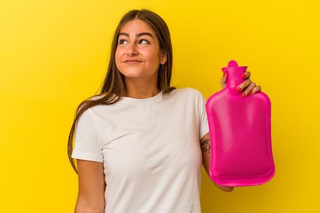 Młoda kaukaska kobieta trzymająca gorącą butelkę wody odizolowana na żółtej ścianie marząca o osiągnięciu celów i celów