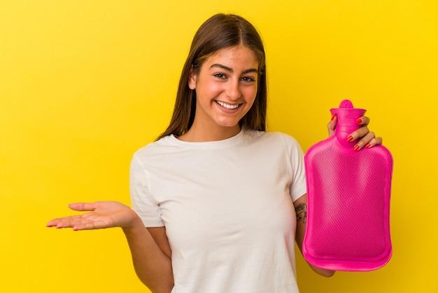 Młoda kaukaska kobieta trzymająca gorącą wodę w butelce odizolowana na żółtej ścianie pokazująca miejsce na dłoni i trzymająca drugą rękę w pasie.