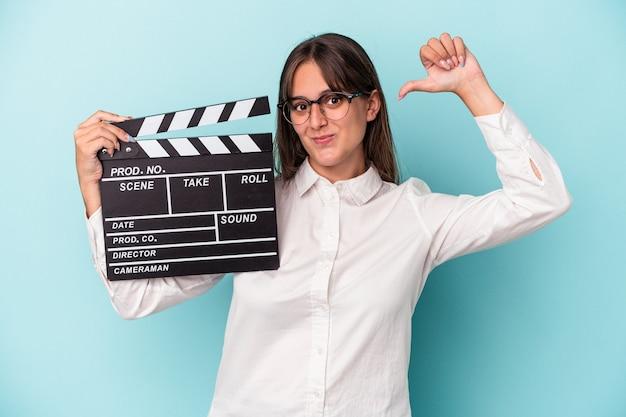 Młoda kaukaska kobieta trzymająca klaps na białym tle na niebieskim tle czuje się dumna i pewna siebie, przykład do naśladowania.