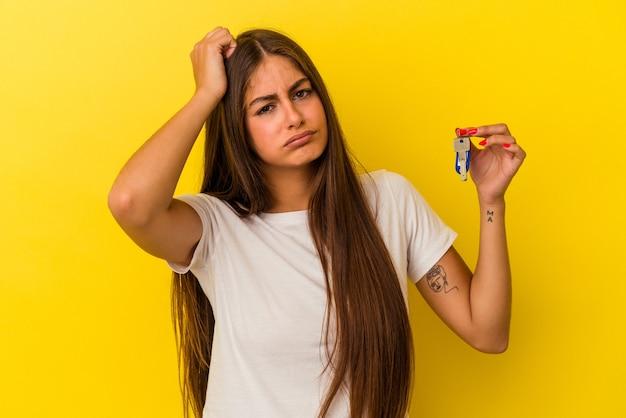 Młoda kaukaska kobieta trzymająca klucze do domu na żółtej ścianie będąc w szoku, przypomniała sobie ważne spotkanie.