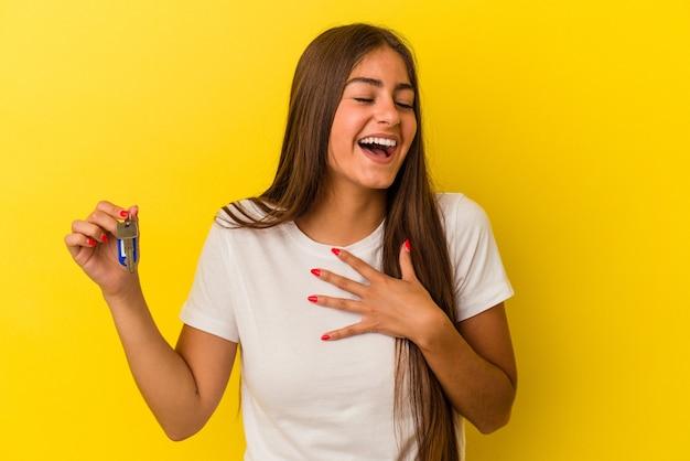Młoda kaukaska kobieta trzymająca klucze do domu na żółtym tle śmieje się głośno trzymając rękę na klatce piersiowej.