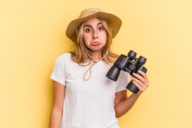 Młoda kaukaska kobieta trzymająca lornetkę na żółtym tle wzrusza ramionami i otwiera oczy zdezorientowana.
