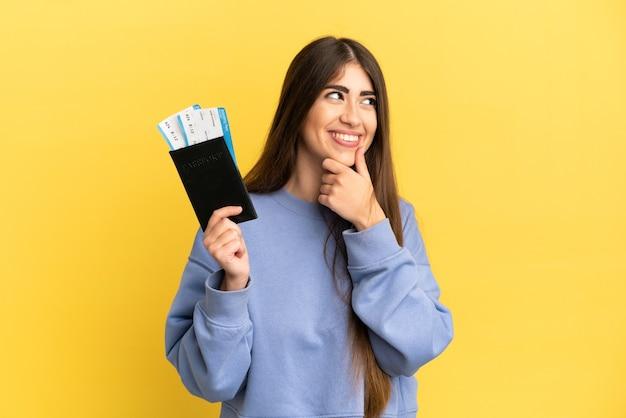 Młoda kaukaska kobieta trzymająca paszport na białym tle na żółtej ścianie, patrząca w bok i uśmiechnięta