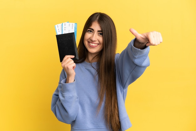 Młoda kaukaska kobieta trzymająca paszport na białym tle na żółtej ścianie, pokazująca gest kciuka w górę