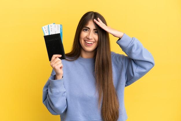Młoda kaukaska kobieta trzymająca paszport na białym tle na żółtej ścianie z wyrazem zaskoczenia