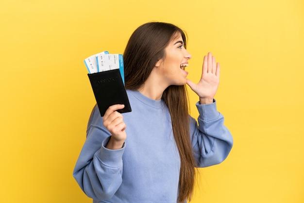 Młoda kaukaska kobieta trzymająca paszport na białym tle na żółtym tle krzycząca z szeroko otwartymi ustami