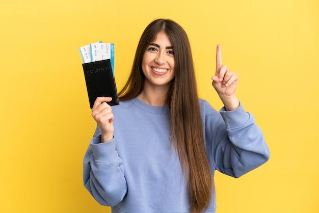 Młoda kaukaska kobieta trzymająca paszport na białym tle na żółtym tle pokazująca i unosząca palec na znak najlepszych