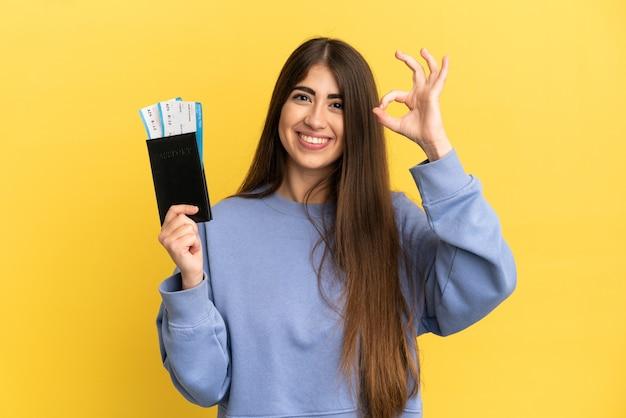 Młoda kaukaska kobieta trzymająca paszport na białym tle na żółtym tle pokazujący znak ok palcami