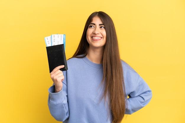 Młoda kaukaska kobieta trzymająca paszport na białym tle na żółtym tle pozująca z rękami na biodrach i uśmiechnięta