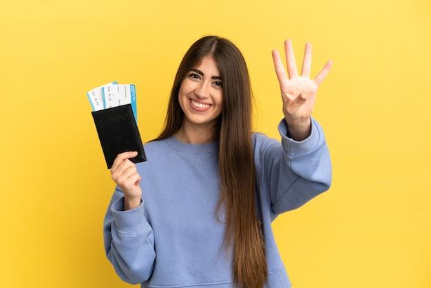 Młoda kaukaska kobieta trzymająca paszport na białym tle na żółtym tle szczęśliwa i licząca cztery palcami