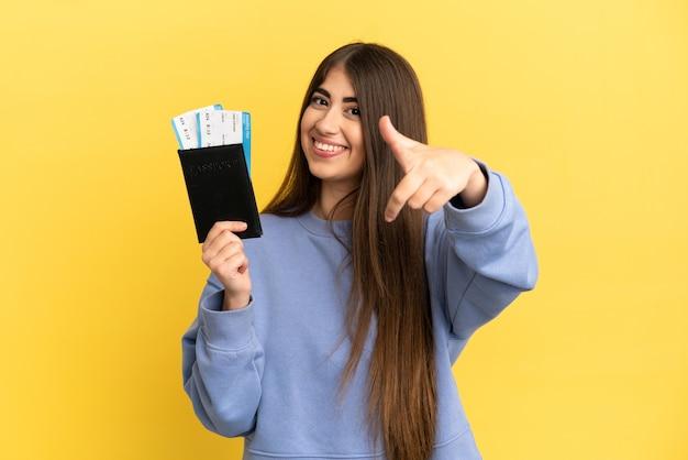 Młoda kaukaska kobieta trzymająca paszport na białym tle na żółtym tle z kciukami do góry, ponieważ stało się coś dobrego