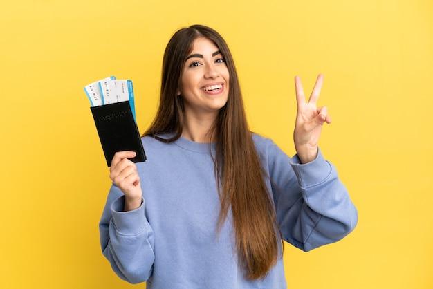 Młoda kaukaska kobieta trzymająca paszport na białym tle, uśmiechnięta i pokazująca znak zwycięstwa