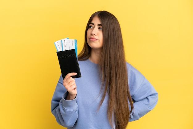 Młoda kaukaska kobieta trzymająca paszport odizolowany na żółtej powierzchni, patrząc w bok