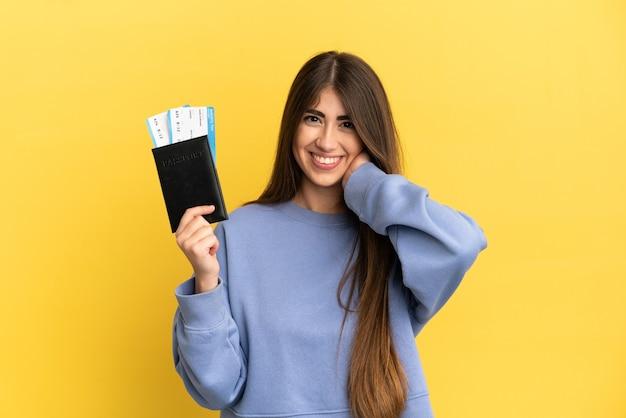 Młoda kaukaska kobieta trzymająca paszport odizolowany na żółtej powierzchni śmiejąc się