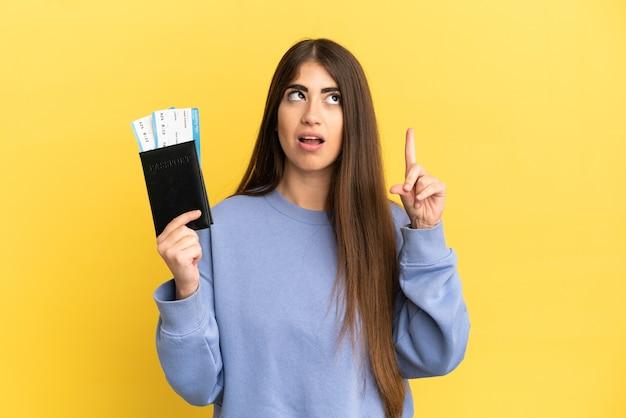 Młoda kaukaska kobieta trzymająca paszport odizolowany na żółtej ścianie, myśląca o pomyśle wskazującym palec w górę