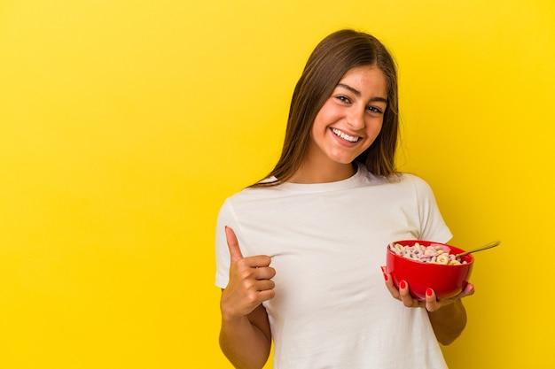 Młoda kaukaska kobieta trzymająca płatki zbożowe na żółtym tle, uśmiechająca się i unosząca kciuk w górę