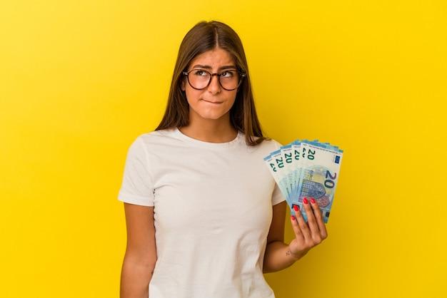 Młoda kaukaska kobieta trzymająca rachunki na żółtym tle zdezorientowana, ma wątpliwości i niepewność.