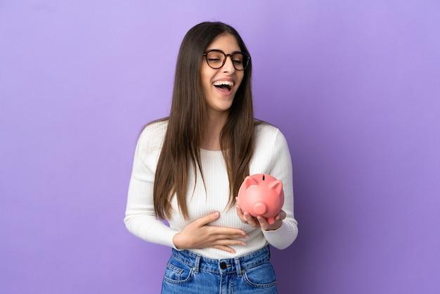 Młoda kaukaska kobieta trzymająca skarbonkę odizolowaną na fioletowym tle dużo się uśmiecha