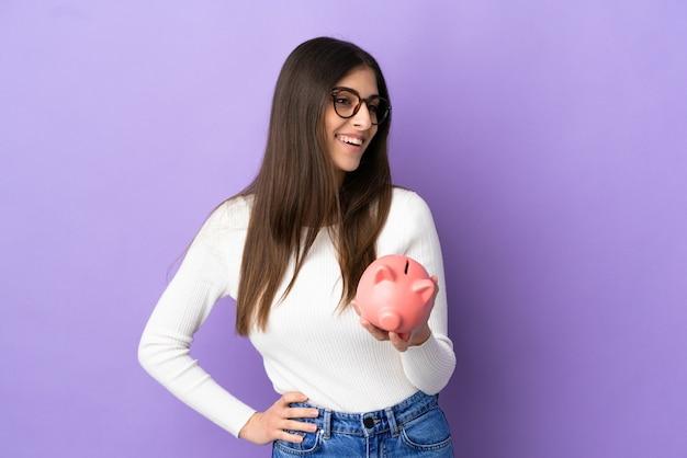 Młoda kaukaska kobieta trzymająca skarbonkę odizolowaną na fioletowym tle pozuje z rękami na biodrach i uśmiecha się