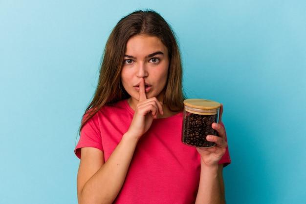Młoda kaukaska kobieta trzymająca słoik kawy na białym tle na niebieskim tle dochowując tajemnicy lub prosząc o ciszę.