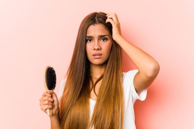 Młoda kaukaska kobieta trzymająca szczotkę do włosów, będąc w szoku, przypomniała sobie ważne spotkanie.