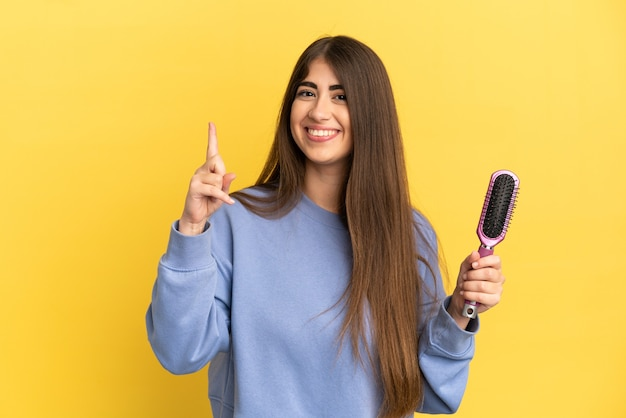Młoda kaukaska kobieta trzymająca szczotkę do włosów na białym tle na niebieskim tle pokazująca i unosząca palec na znak najlepszych