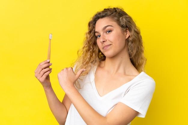 Młoda kaukaska kobieta trzymająca szczotkowanie zębów na żółtym tle dumna i zadowolona z siebie