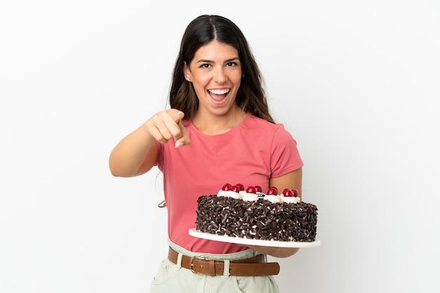 Młoda kaukaska kobieta trzymająca tort urodzinowy na białym tle zaskoczona i wskazująca przód