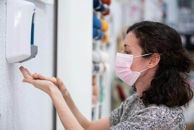 Młoda kaukaska kobieta ubrana w higieniczną maskę na twarz i używając żelu dezynfekującego do mycia rąk