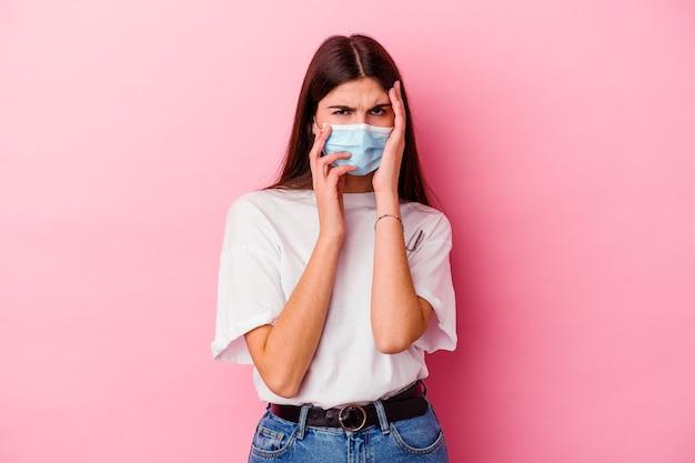 Młoda kaukaska kobieta ubrana w maskę wirusa na różowym skomle i płacze niepocieszony.