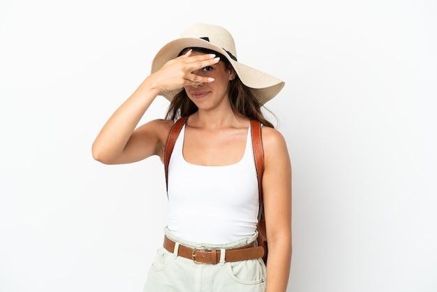 Młoda kaukaska kobieta ubrana w pamelę podczas letnich wakacji na białym tle zakrywająca oczy rękami i uśmiechnięta