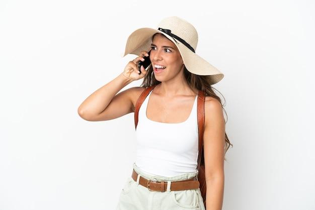 Młoda kaukaska kobieta ubrana w pamelę w letnie wakacje na białym tle, prowadząca rozmowę z telefonem komórkowym z kimś