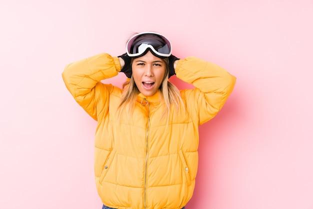 Młoda kaukaska kobieta ubrana w strój narciarski w różowej ścianie zakrywającej uszy rękami, starając się nie słyszeć zbyt głośnego dźwięku.