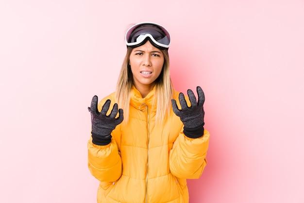 Młoda kaukaska kobieta ubrana w stroje narciarskie w różowej ścianie zdenerwowany krzycząc z napiętymi rękami.