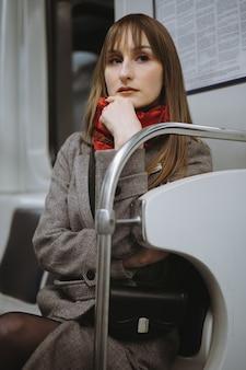 Młoda kaukaska kobieta w eleganckim płaszczu, siedząca samotnie w wagonie metra