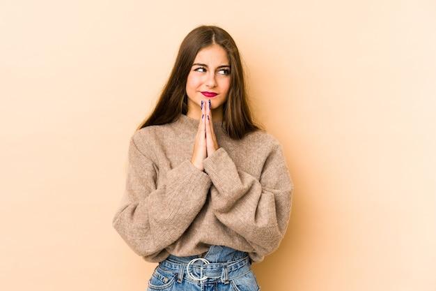 Młoda kaukaska kobieta w kolorze beżowym modląca się, okazująca oddanie, osoba religijna poszukująca boskiej inspiracji.