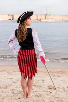 Młoda kaukaska kobieta w pasiastym pirackim kostiumu obniżyła zabawkowy miecz na plaży.