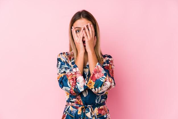 Młoda kaukaska kobieta w piżamie mruga palcami przestraszonymi i nerwowymi.
