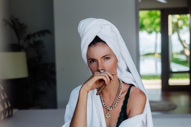 Młoda kaukaska kobieta w pokoju hotelowym w szlafroku i białym ręczniku miała z cygarem.