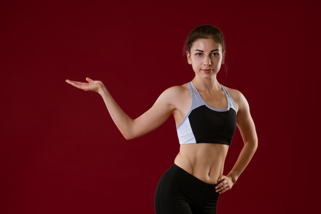 Młoda kaukaska kobieta w stroju sportowym na czerwonym tle pokazuje swoją rękę na bok koncepcja...